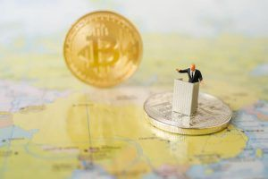 Miniature people: A Businessman speech on podium with Global World map   and Bitcoin background. Success Business Due and New Technology Money   transfer concepts.