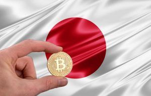 hand holding a bitcoin with japan flag background
