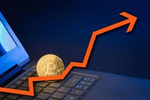 bitcoin standing upright on laptop keyboard with arrow pointing up
