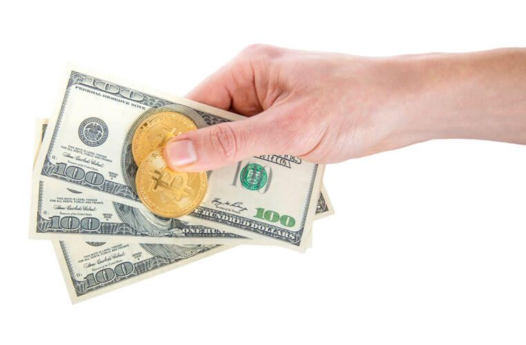 two golden Bitcoin on US dollars in a man hand. Digitall symbol of a new virtual currency.Electronic money exchange concept. isolated on white background
