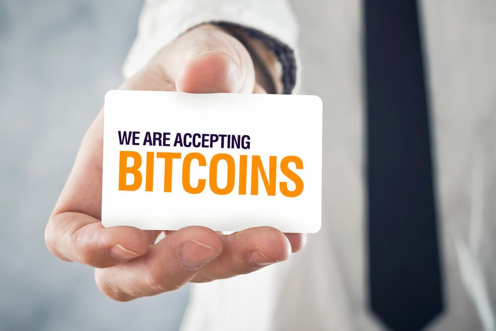 "Businessman holding card with title ""WE ARE ACCEPTING BITCOINS"""