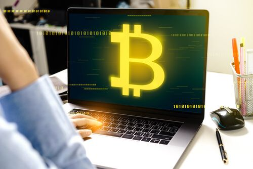 Woman using modern laptop computer with Bitcoin