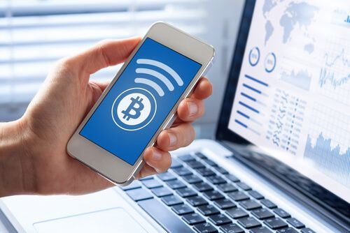 Person sending bitcoin with smartphone for online payment