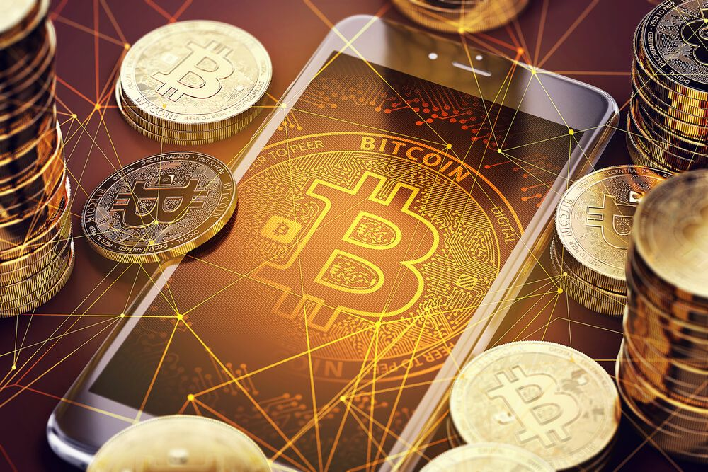 Smartphone with Bitcoin on-screen among piles of Bitcoins.