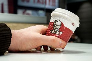 Cup of coffee with logo KFC in hand in a restaurant KFC