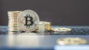 Bitcoin symbol among piles of golden coins