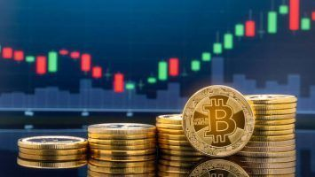 Bitcoin and cryptocurrency investing concept - Physical metal Bitcoin coins with global trading exchange market price chart.