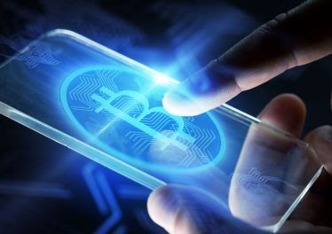 close up of hands with virtual bitcoin symbol hologram transparent smartphone screen over black background