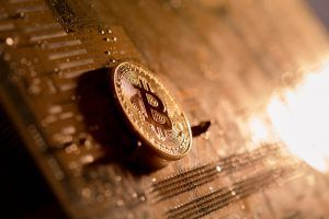 Golden Bitcoin on a wooden table.
