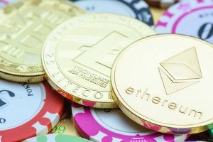 Crypto currency, blockchain / digital money concept : Golden coins e.g Bitcoin BTC, Ethereum ETH, Litecoin LTC on casino tokens or chips, depicts risk in trading / investing or gambling virtual assets