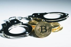 Golden bitcoin coin with Handcuffs on the white background.