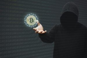Hacker reach out to grab bitcoin coin.