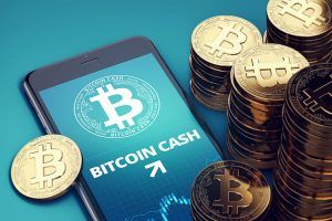 Smartphone with Bitcoin Cash growth chart on-screen among piles of golden Bitcoin Cash coins. BCC/BCH growth concept.
