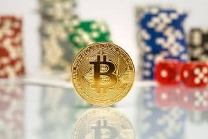 Bitcoin crypto currency high risk investment concept, golden bitcoin coin in front of stacks of poker playing chips and red pair of dice, volatile cryptocurrency market conceptualisation, bad call