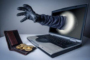 The abstract image of the hacker's hand reach through a laptop screen for stealing bitcoin in a wallet. the concept of cyber attack, virus, malware, cryptocurrency, illegally and cyber security.