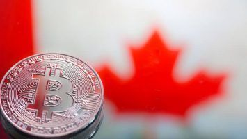 coins Bitcoin, against the background of Canada flag, concept of virtual money, close-up. Conceptual image of digital crypto currency.