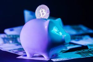 Bitcoin in the slot of a piggy bank standing on a pile of euro bills. Conceptual closeup image for worldwide cryptocurrency and digital payment system. Unique blue/violet lighting. Side view.