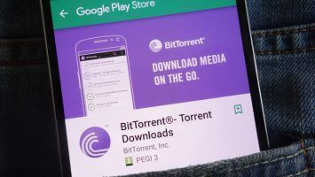 BitTorrent app on Google Play Store website displayed on smartphone hidden in jeans pocket