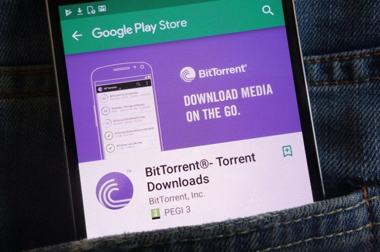 BitTorrent app on Google Play Store website displayed on smartphone hidden in jeans pocket