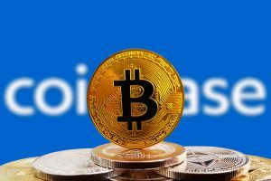 Bitcoin BTC on stack of cryptocurrencies with Coinbase logo in background. The cryptocurrency coin is golden and in focus