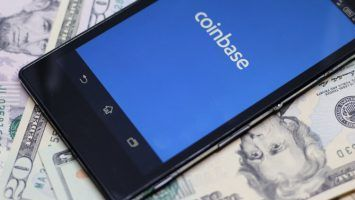 Coinbase android app on dollar background. Coinbase is a digital currency exchange.