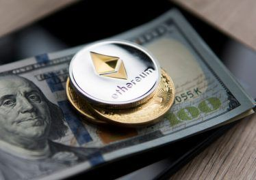 Ethereum coin on a us dollars and on the tablet with golden coins. Bitcoin crypto currebcy on US dollars. Digital currency. Virtual money. Metal coins of bitcoin on banknotes. Bussiness, commercial.