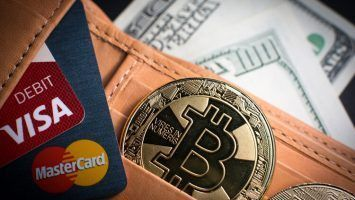 Bitcoin. Gold coin with bitcoin symbol cash and credit / debit cards Visa and MasterCard in a wallet