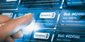 Finger pressing a block chain block with the text transaction, a bitcoin symbol and security sha256 algorithm hach. Composite between a hand photography.