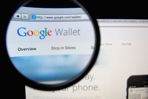 Google Wallet homepage on a monitor screen through a magnifying glass