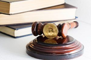 Judge's hammer and bitcoin gold coin.