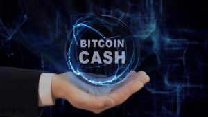 Painted hand shows concept hologram Bitcoin cash on his hand. Drawn man in business suit with future technology screen and modern cosmic background