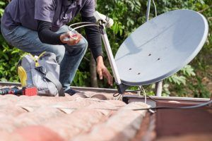 Skillful technician worker installing satellite dish and television antenna on roof top