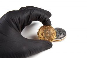 Hand in black glove raising Bitcoin.