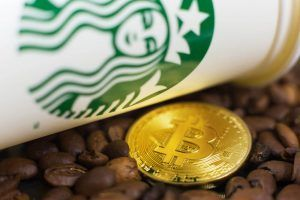 Cryptocurrency Bitcoin on coffee beans with Starbucks cup. Slovenia