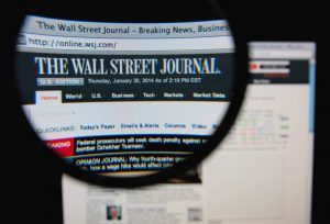 Wall Street Journal homepage on a monitor screen through a magnifying glass.