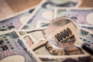 Japanese Yen Banknotes shot stack layers on floor with magnifying glass for selective focus