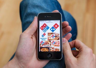 male hand holding iPhone with Domino's pizza delivery images in Google search on the display.