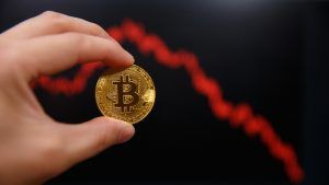 Man holding a Bitcoin with falling price chart in the background.