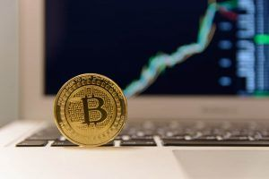 Bitcoin on a laptop with rising price chart in the background.