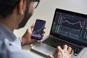 An image featuring a crypto broker using his laptop and phone watching the financial market