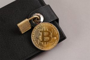 An image featuring a wallet that has a lock on it with a bitcoin next to it representing secure crypto wallet concept