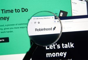 An image featuring a magnifying glass on the Robinhood homepage