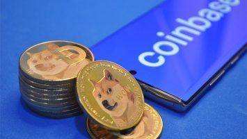 An image featuring Dogecoins next to a phone that has the Coinbase platform opened
